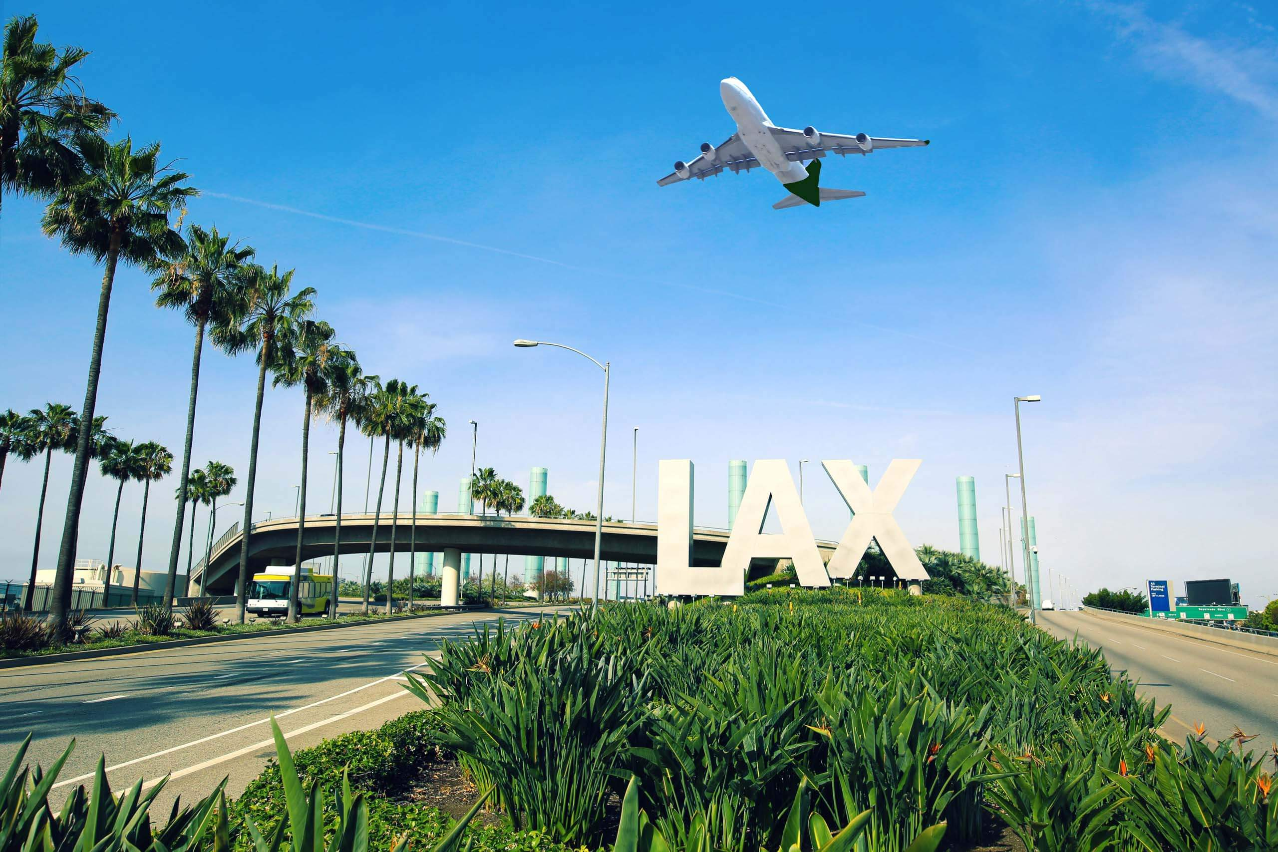 Los Angeles Airport sign full highway with airplane flying overhead.