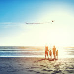 Shot of a family of four watching a kite flying in the sky at the beach.