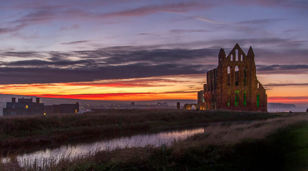 Illuminted image of the ruined Whitby Abbey against a sunset sky