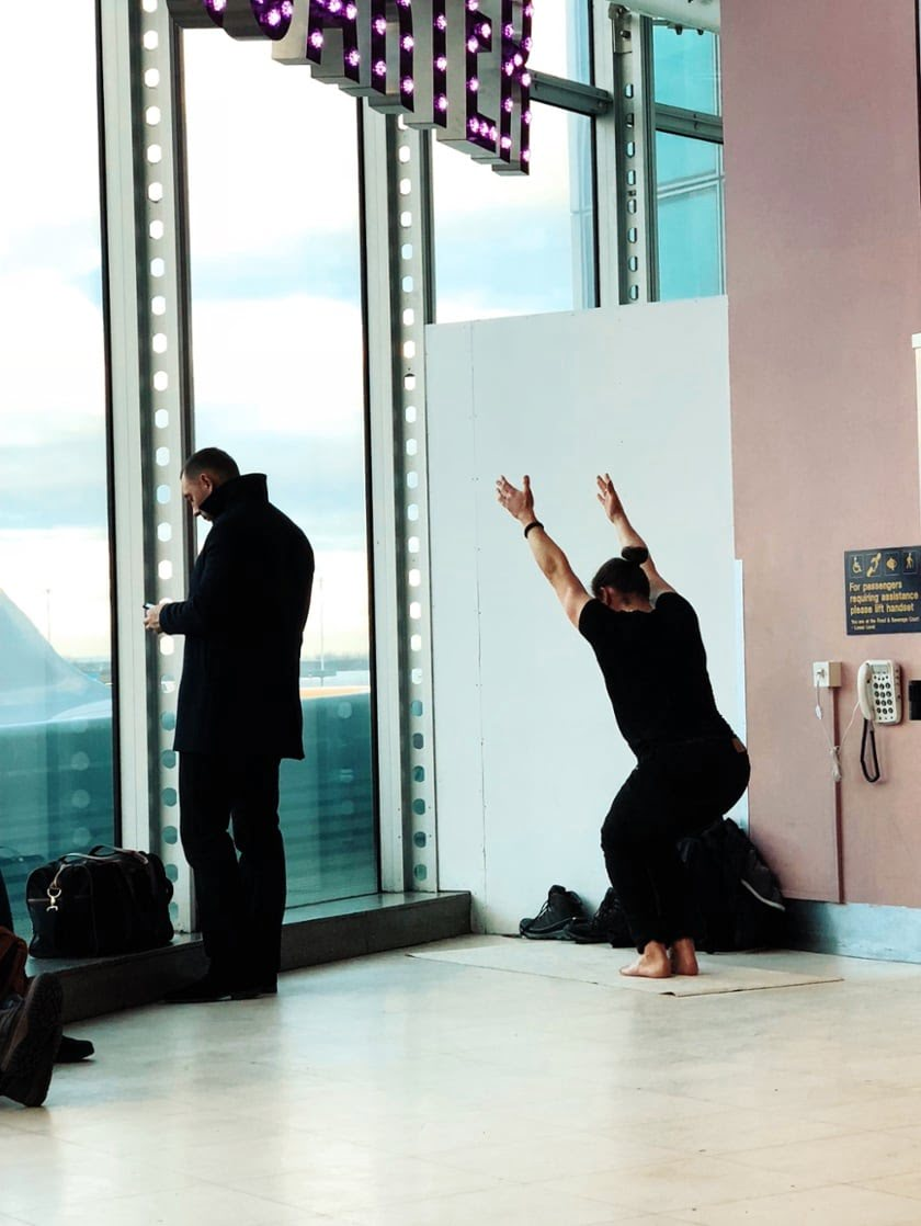 Man doing Yoga in an airport terminal. Photo by Jon Tyson on Unsplash