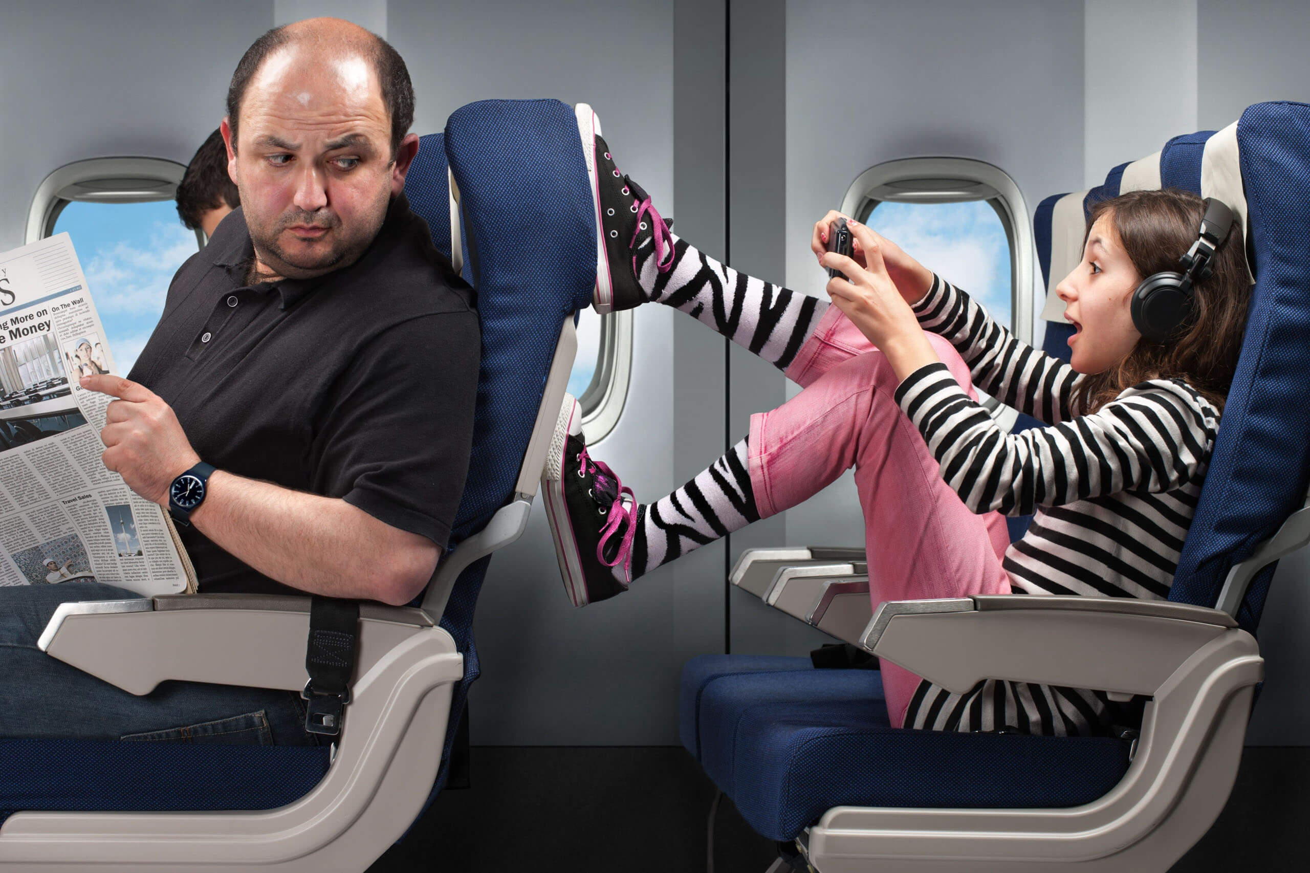 Young girl kicking aeroplane seat