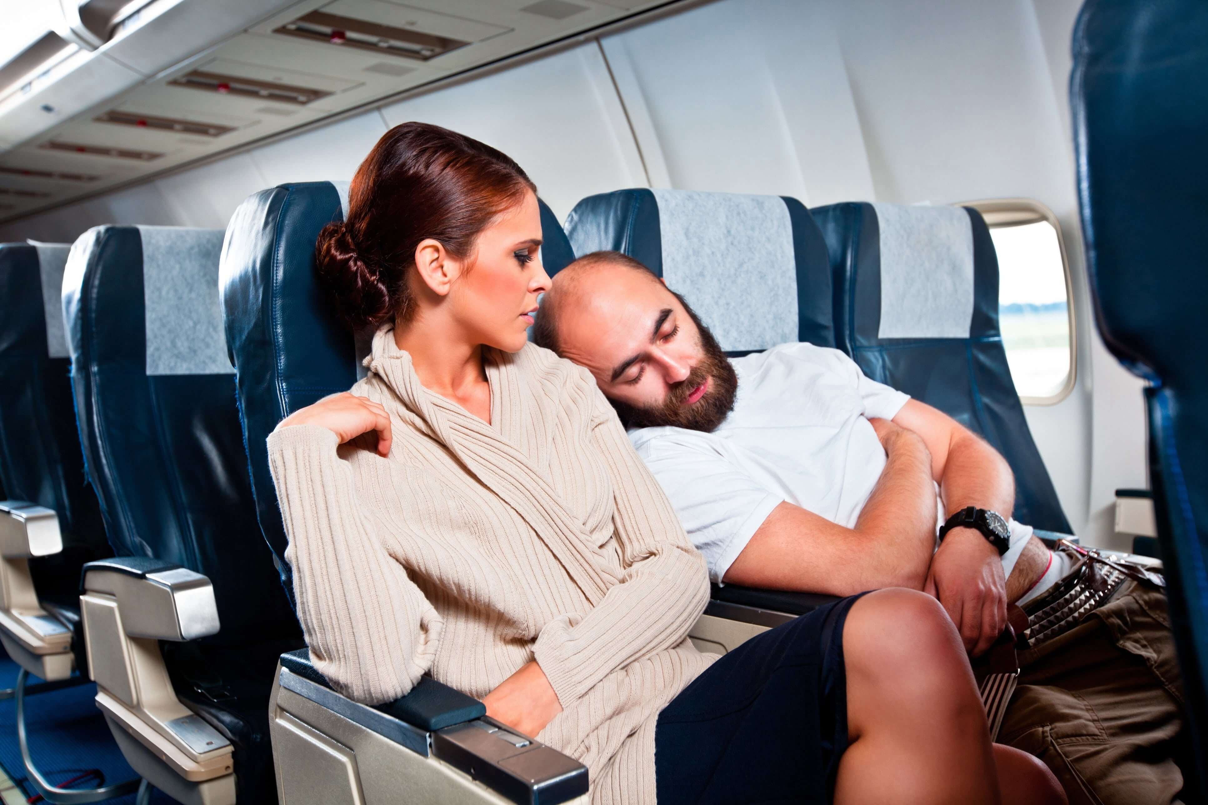 Man falling asleep on woman on plane