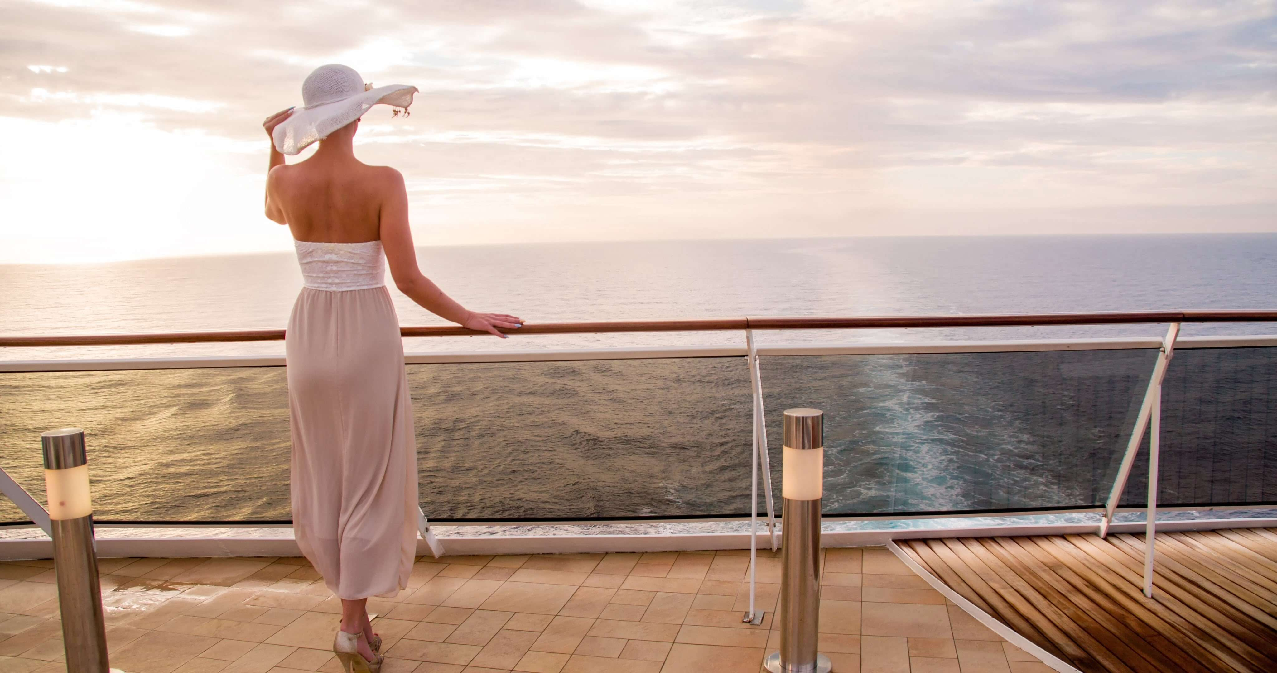 A woman looks out to sea from the deck of a ship