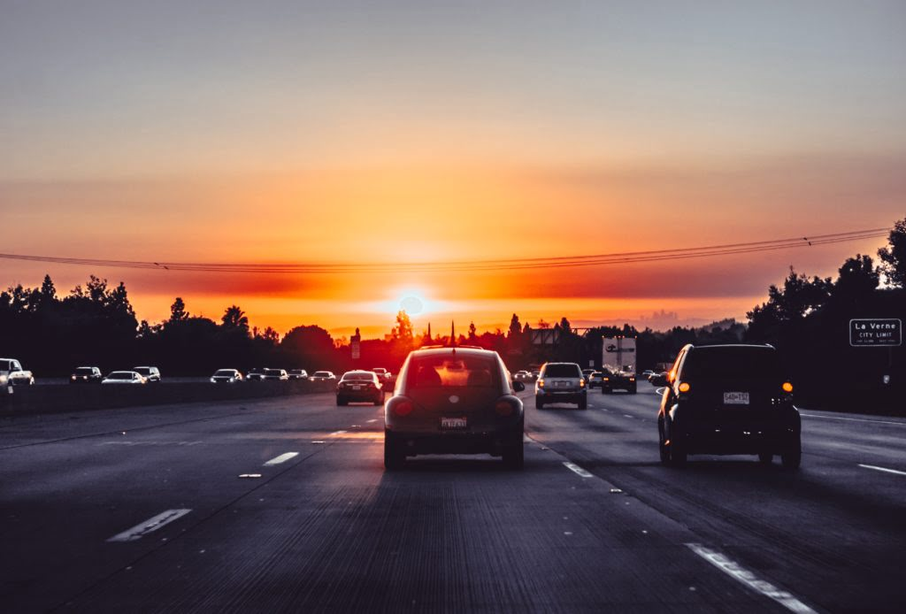 Cars driving into sunset. Photo by Xan Griffin on Unsplash