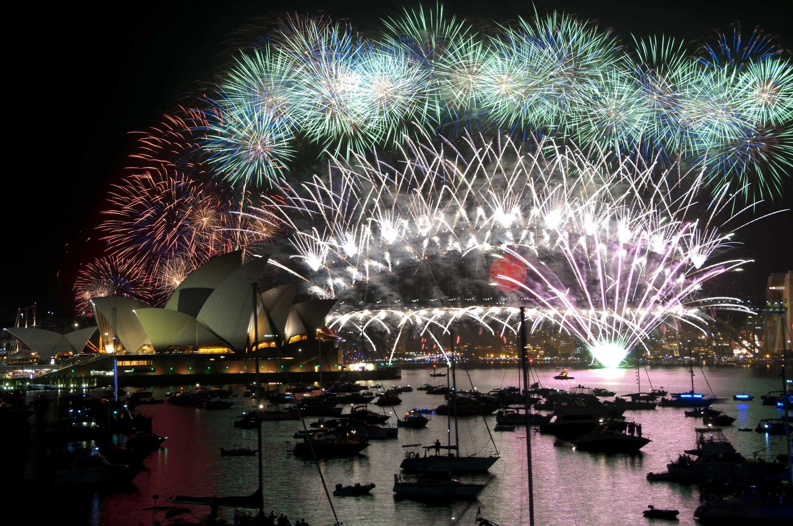 New Year's Eve fireworks from the Harbour Bridge and over Sydney Harbour, with reflections on the water