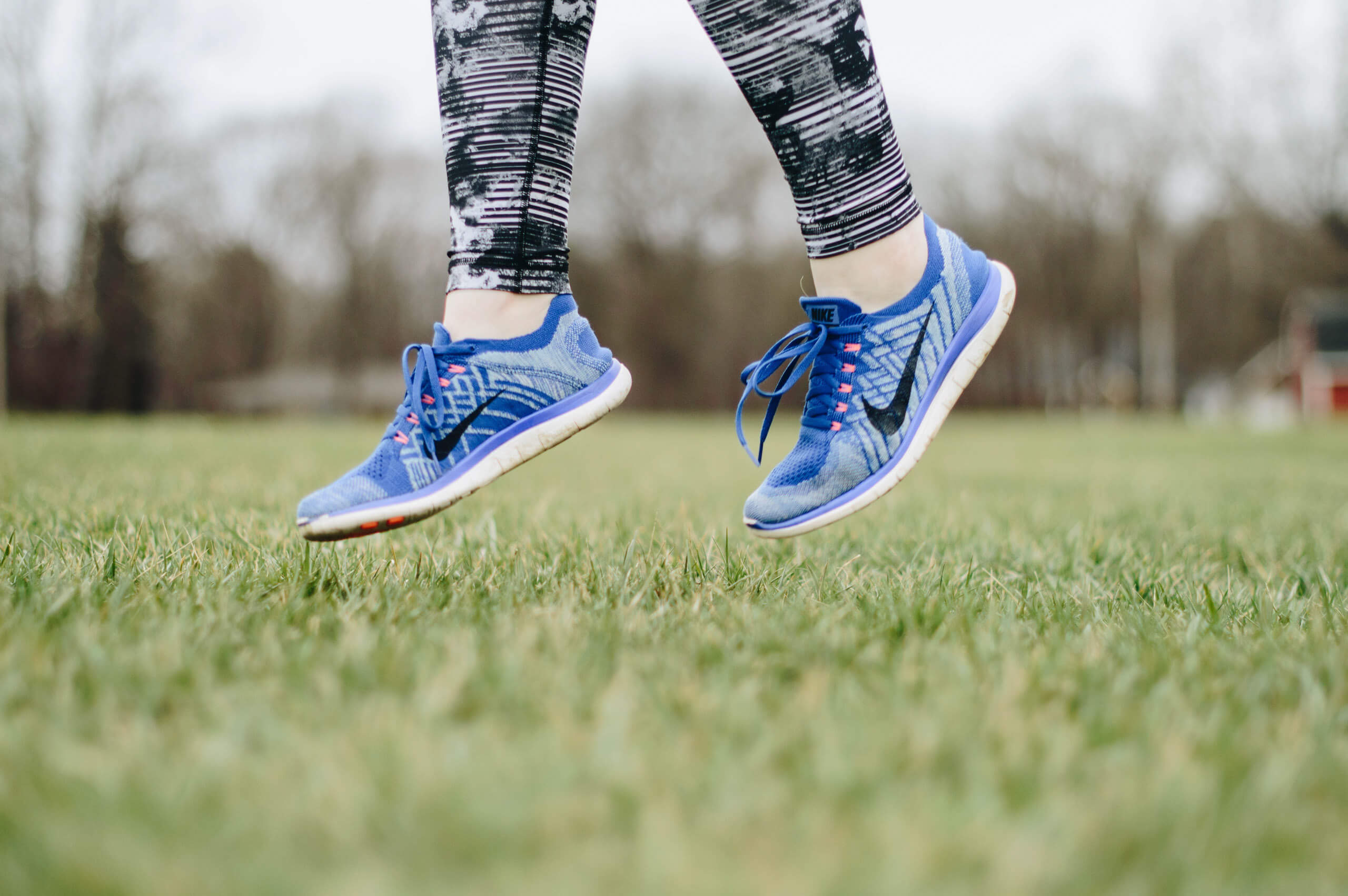 Nike shoes jumping in green field