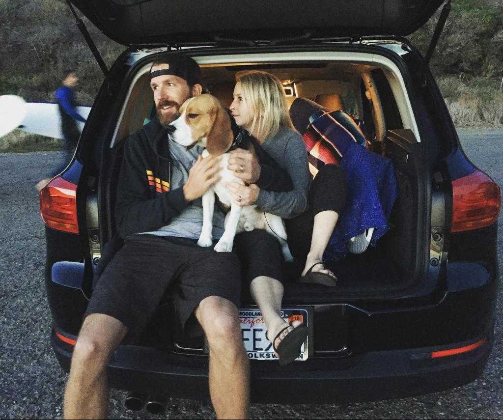 Lauren, Mike and their dog Stevie Beagle sitting in the back of their car at the beach