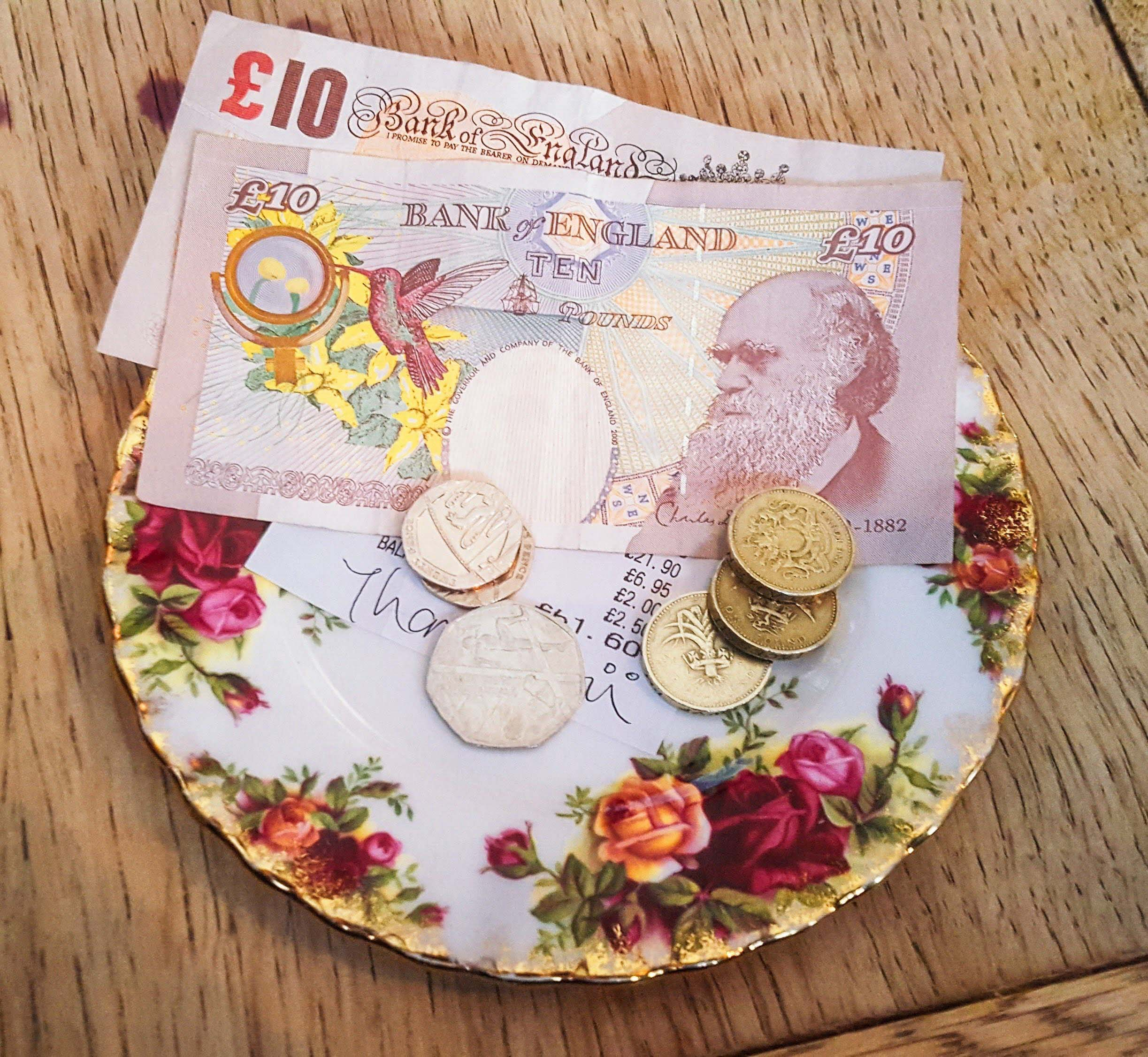 English notes and coins on a floral plate Third image: Tube sign