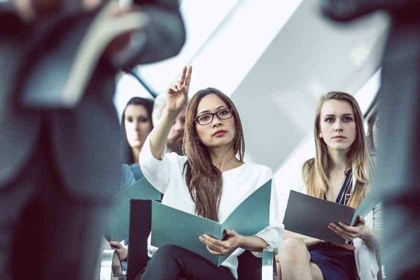 women asking questions at business conference