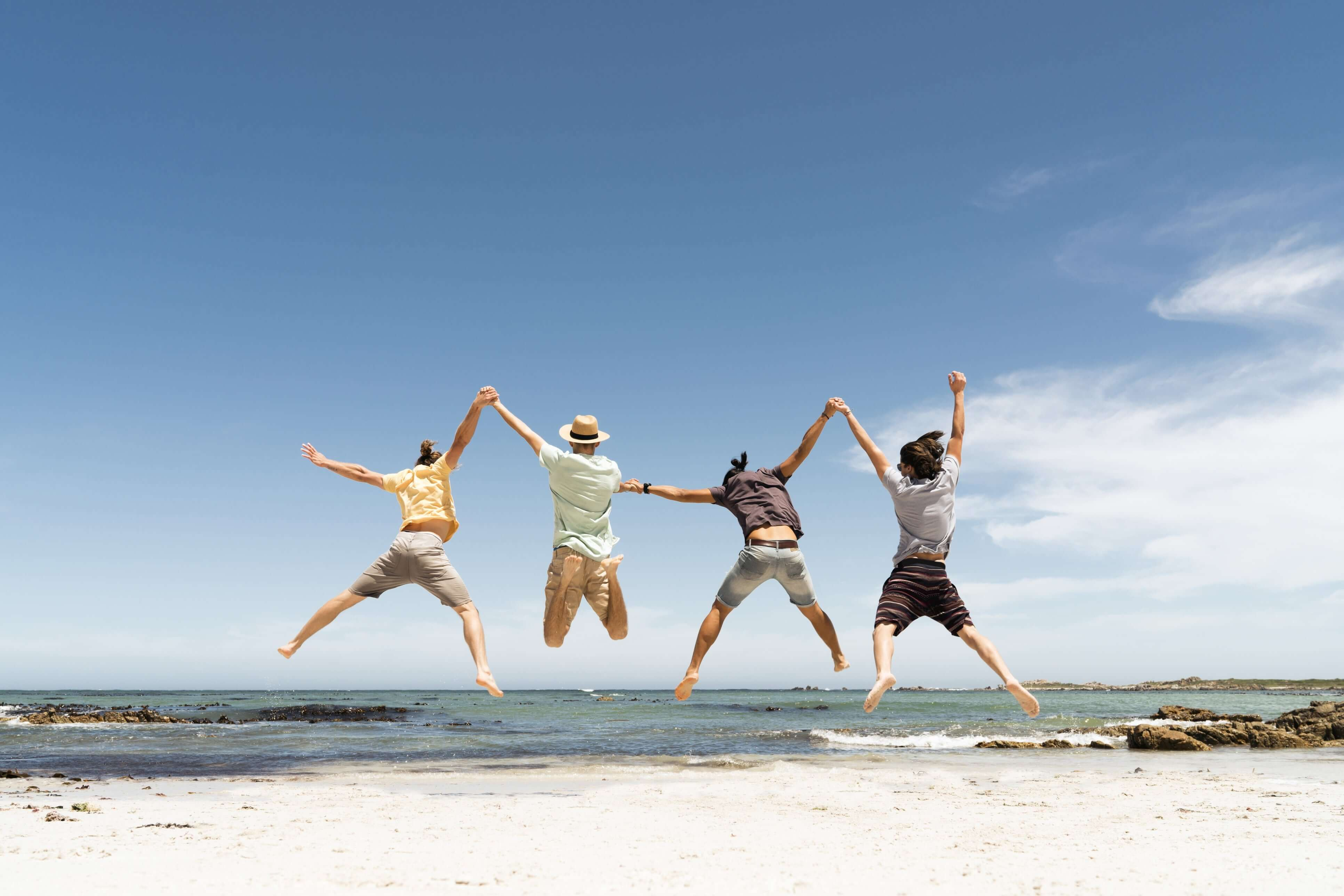 Friends jumping at the beach