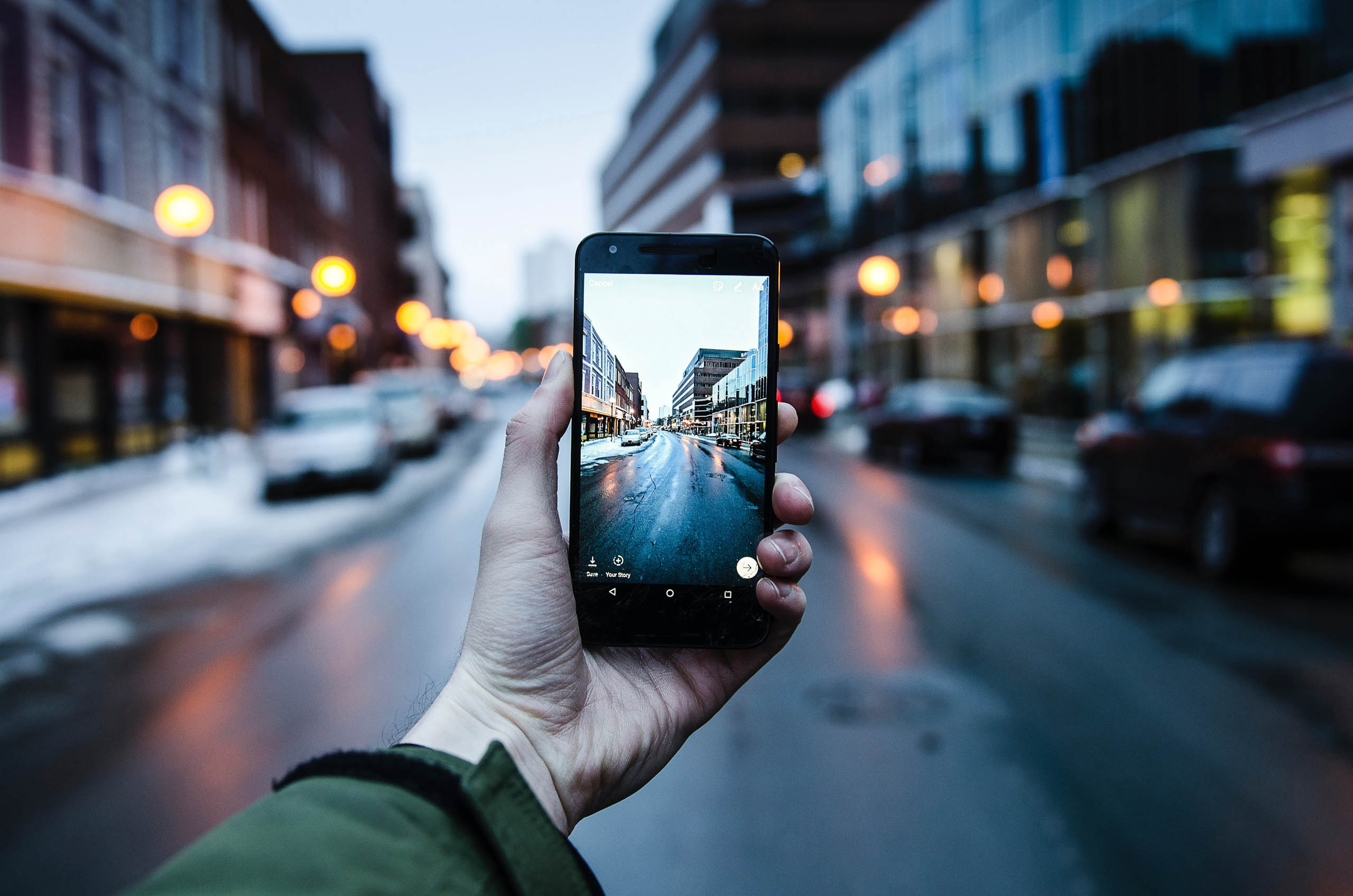 Man holding a phone, with a view of a street through the phone