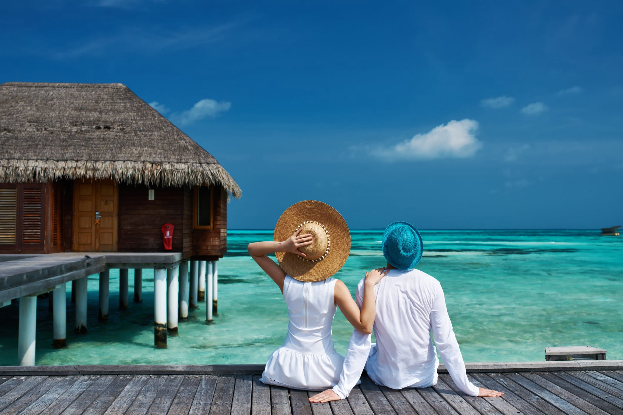 Romantic couple sitting on beach jetty on tropical island