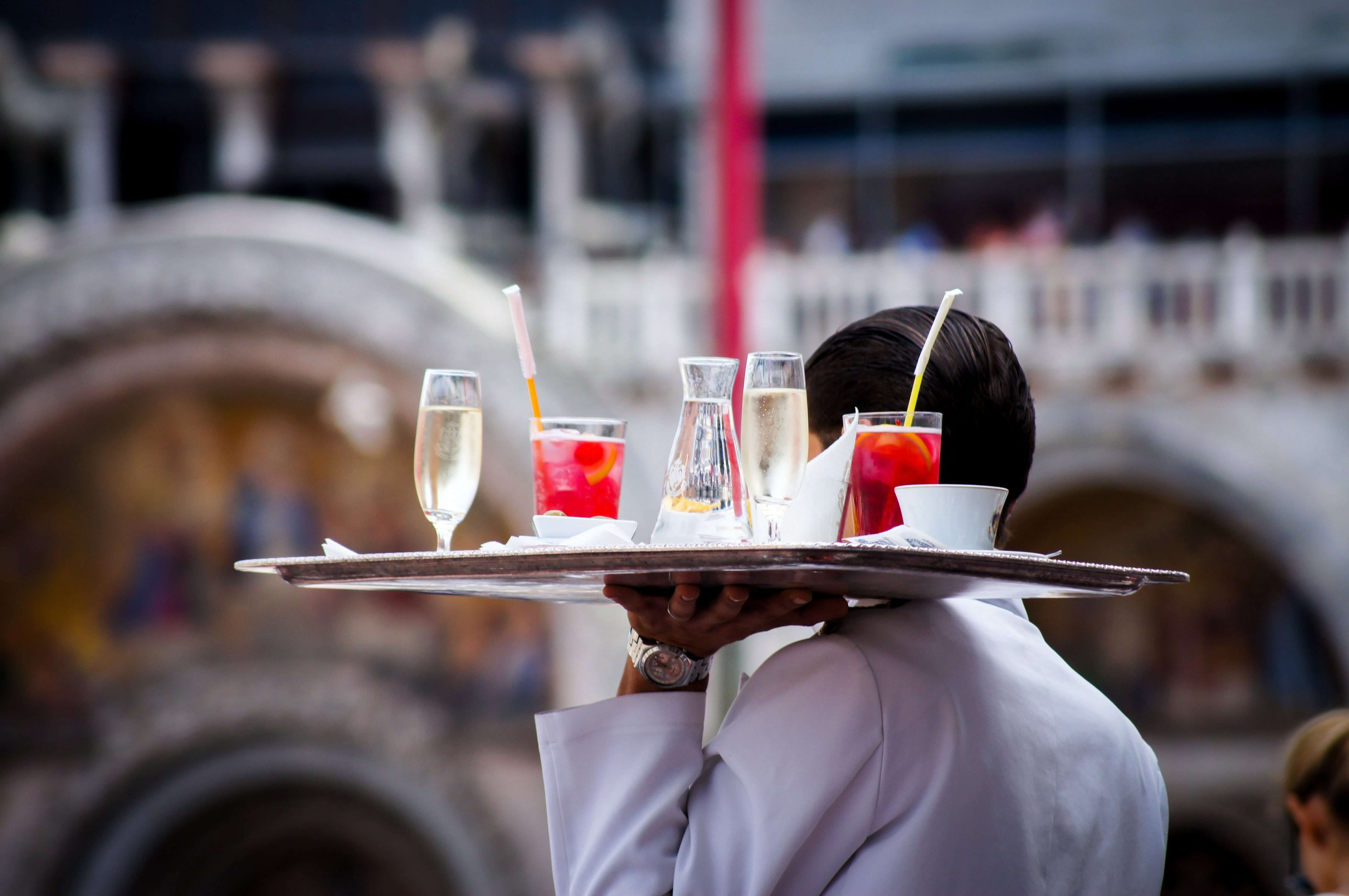 Waiter carrying a tray of drinks. Photo by Kate Townsend on Unsplash