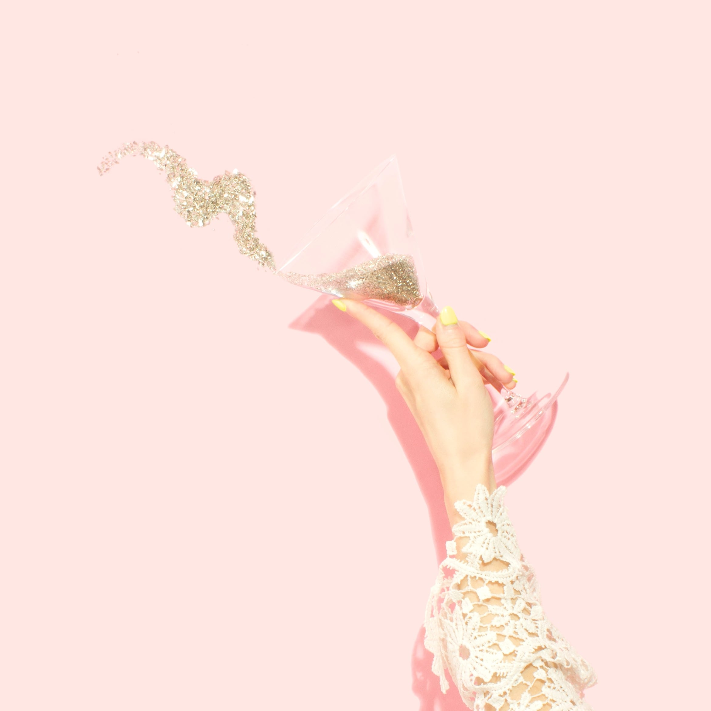 Woman holding martini glass filled with glitter. Photo by Amy Shamblen on Unsplash