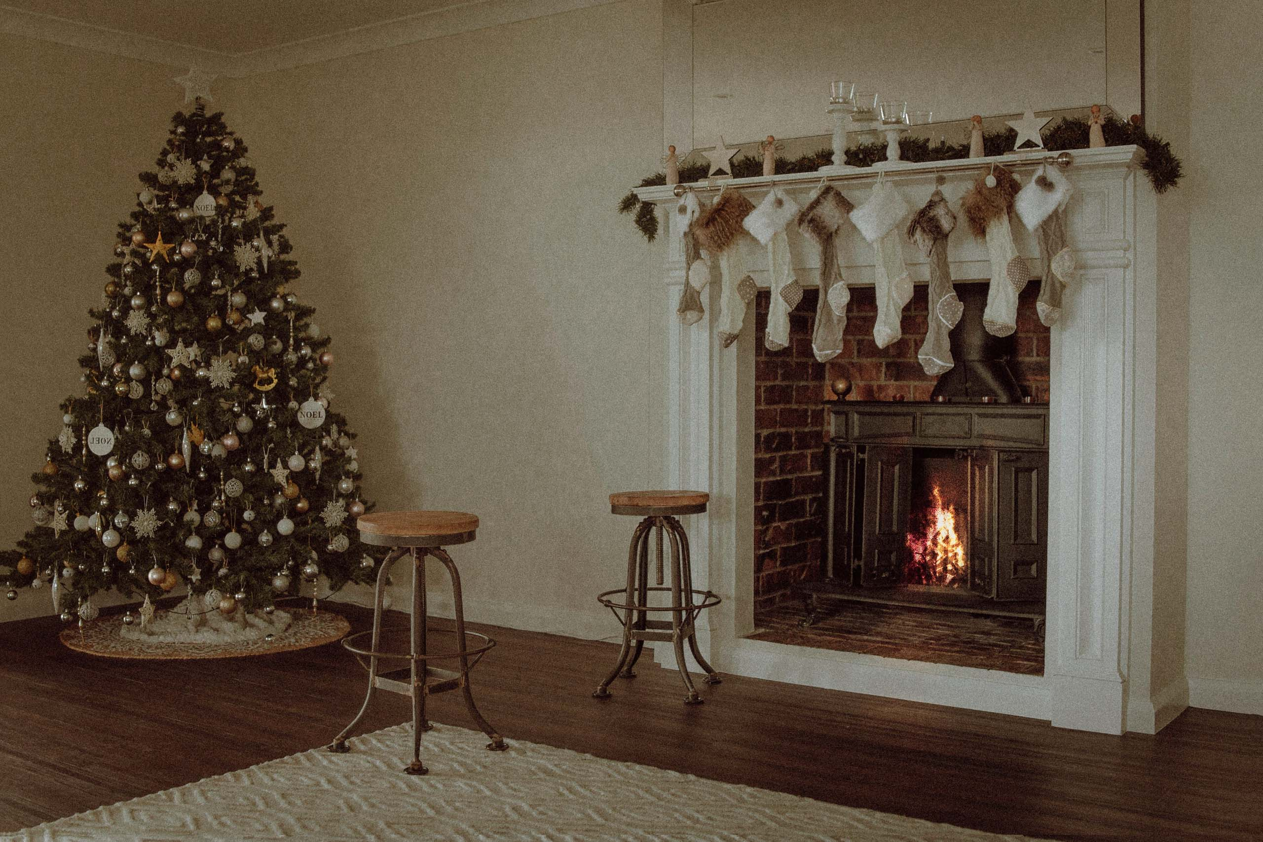 Christmas tree with stockings hanging up over fireplace. Photo by Kyle Head on Unsplash