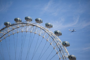 View of the London Eye with a plane flying above