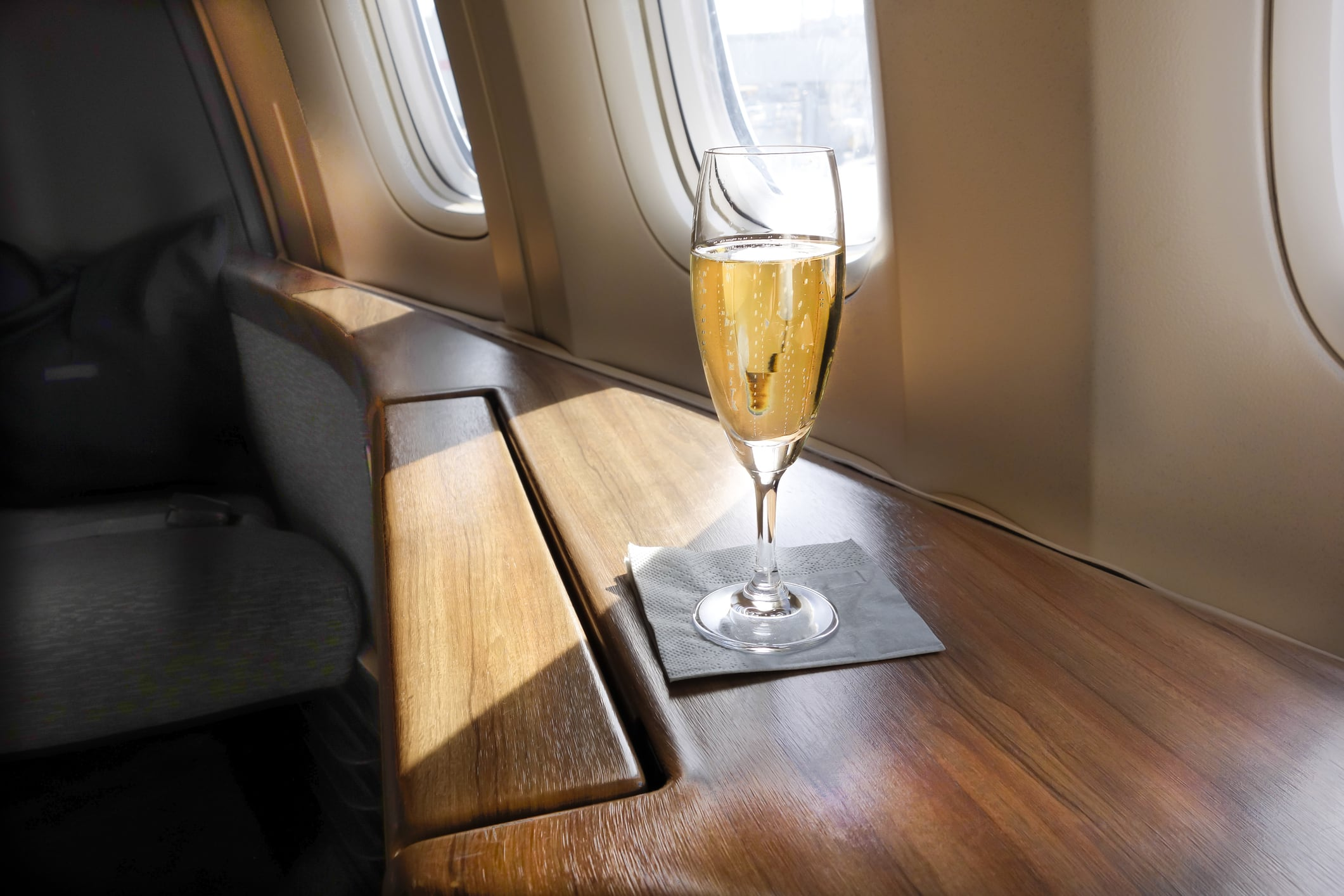 Glass of champagne in a business class cabin inside a plane