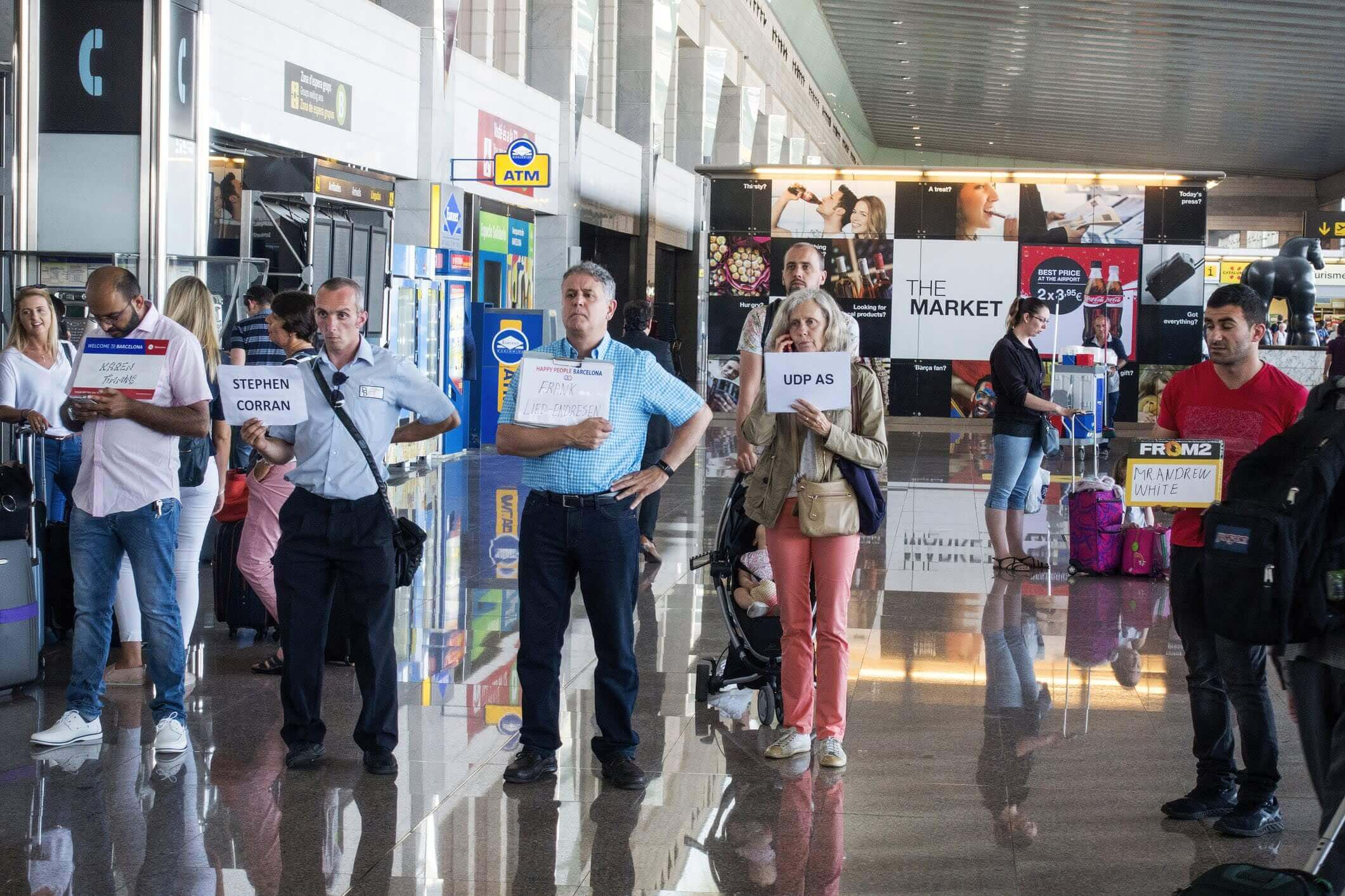 People waiting for arriving passengers at airport holding signs