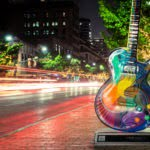 Lit-up guitar sign on busy road in Austin
