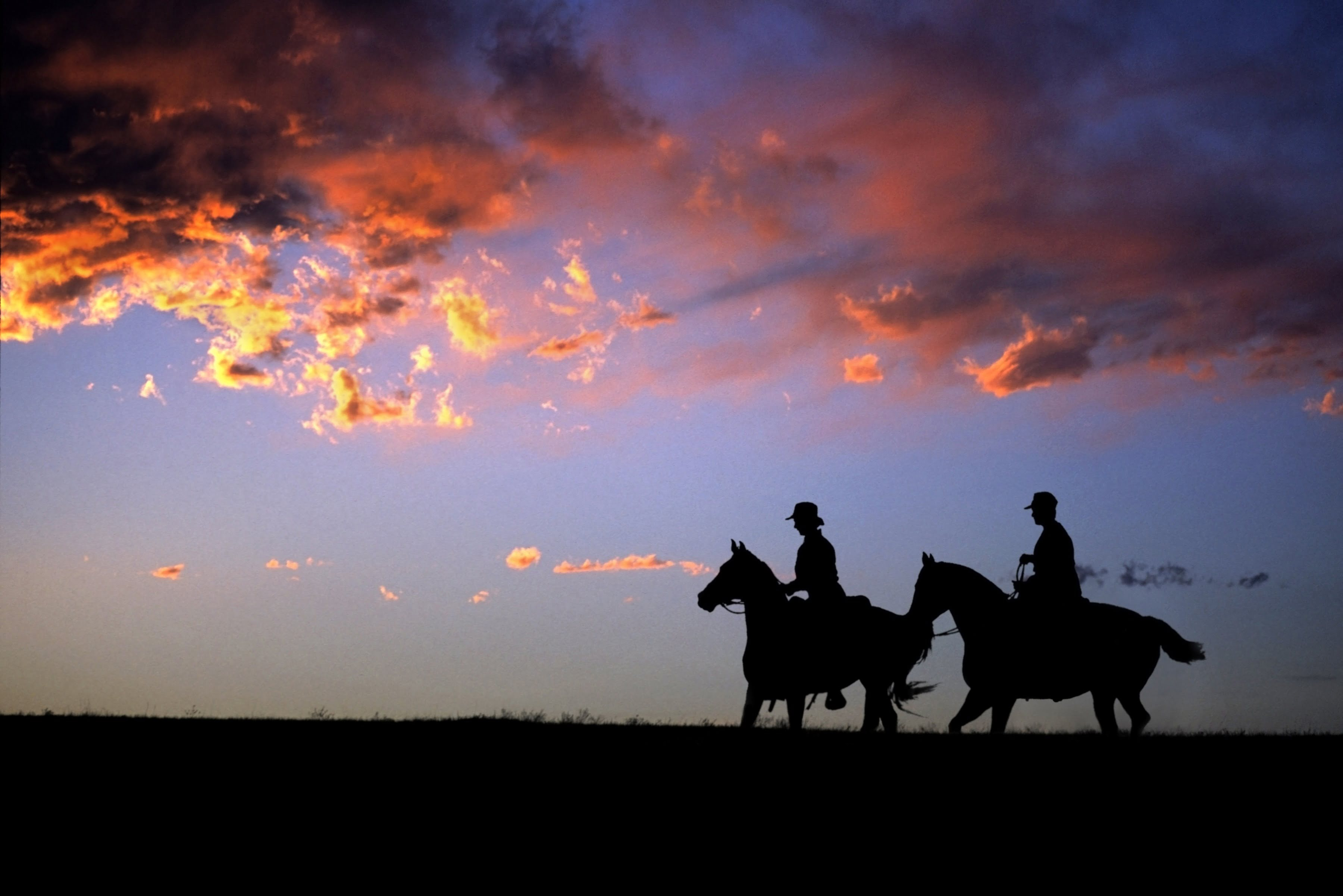 Two people horseback riding at sunset
